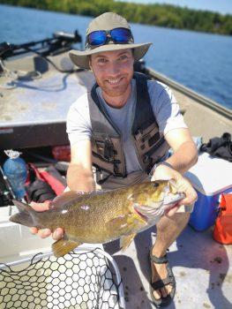 Un étudiant souriant, tenant un poisson dans un bateau