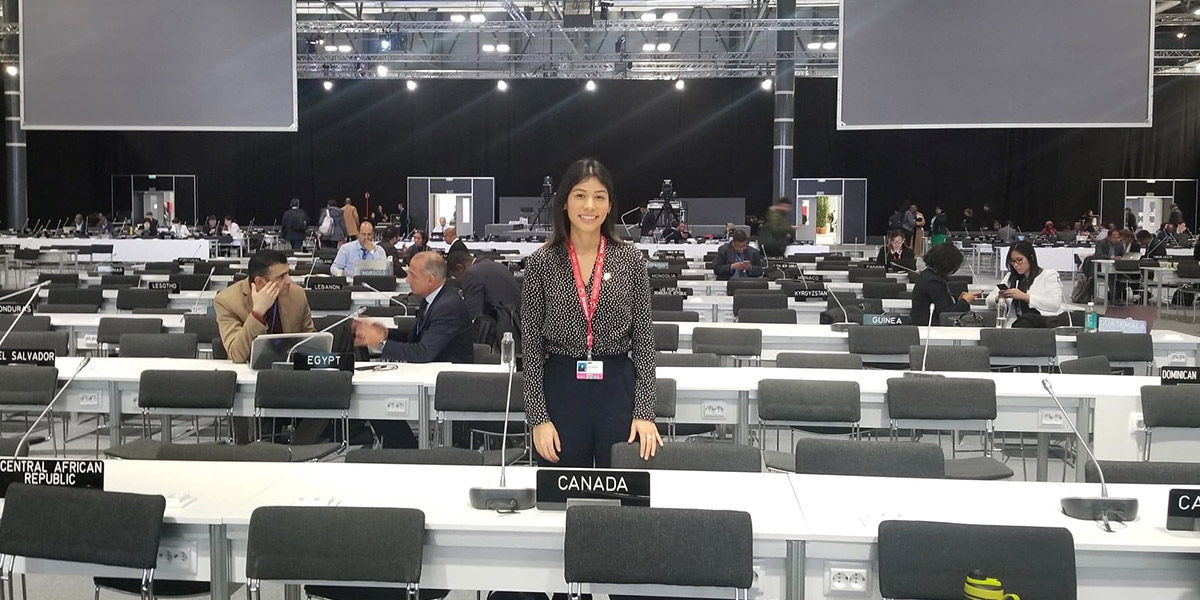 Maria standing behind a signed saying Canada