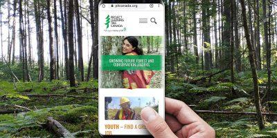 une main tient un téléphone devant une forêt. Au téléphone, le nouveau site Web de PLT Canada