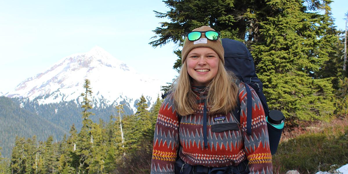 Une femme souriante, debout devant un arbre avec une montagne en arrière-plan.