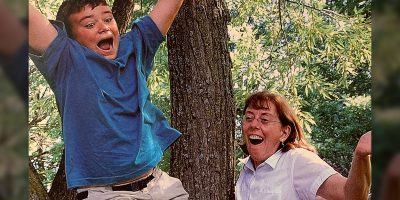 Kevin Southgate as a youth jumping ecstatically in the forest with his aunt in the background