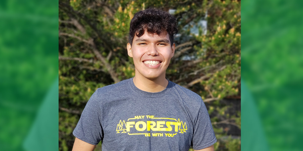 "head and shoulders shot of Lucas wearing a t-shirt that reads ""May the Forest Be With You"""