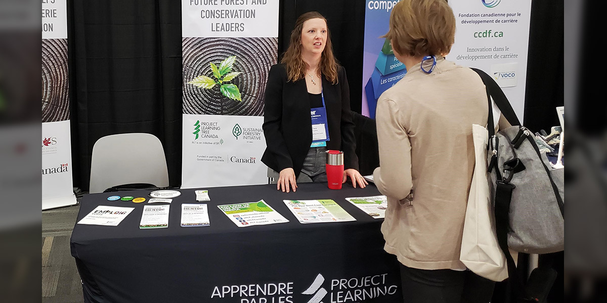 Tara speaks with a conference delegate at the PLT Canada booth.