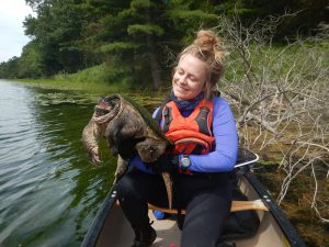 Amy Hall in a canoe holding a big turtle.