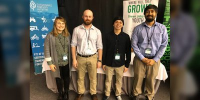amy hall and three young men in front of PLT Canada conference booth