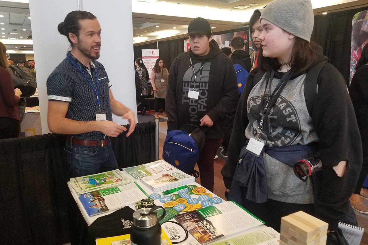 Paul parle avec une jeune femme autochtone au kiosque de PLT Canada lors de l'événement de vol à voile Indspires 2020