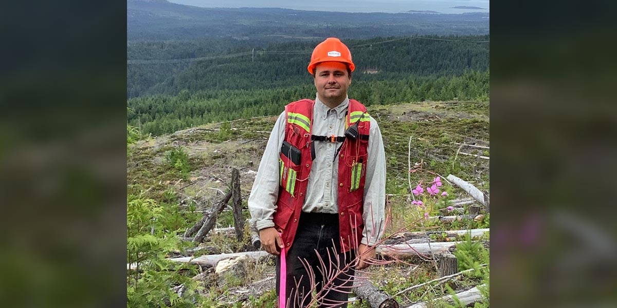 Young man in a high vis vest, hard hat and gear stands on a hill with forest in the background.