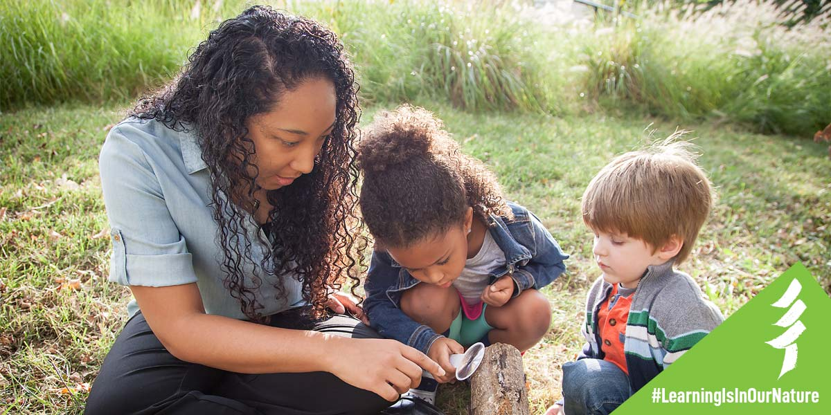 An adult woman inspects a rock outdoors with two small children and a magnifying glass