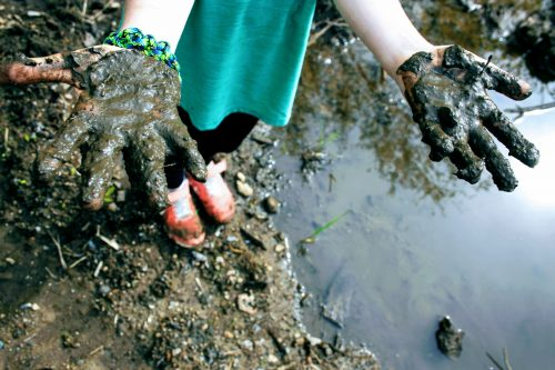 A child shows the camera her muddy hands as she stands on mud near a puddle.