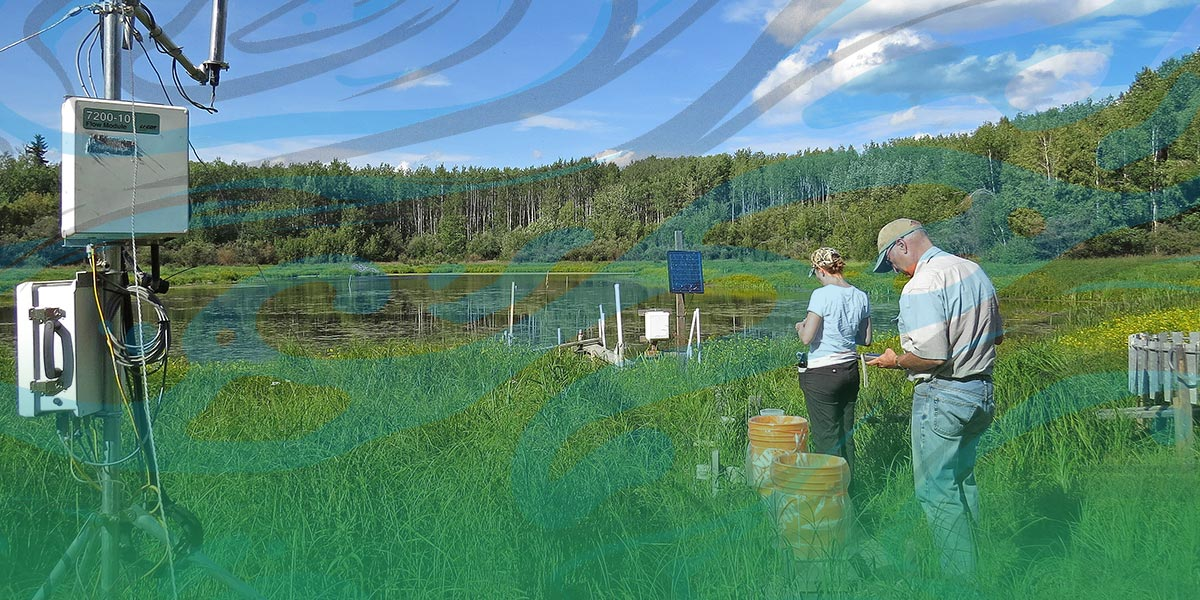 a man and woman in t-shirts and jeans stand by a small lake with scientific equipment