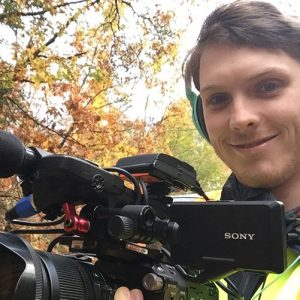 Young man holding a video camera in the forest