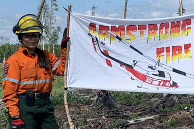 A young person in firefighting gear holds an Armstrong Fire flag