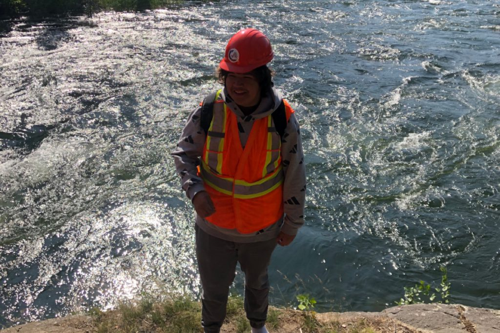 A young person stands in front of a river wearing a hard hat and a vest