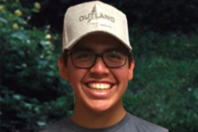 A young person smiling in an Outland baseball cap