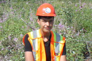 A young person sitting in the forest, wearing a vest and hard hat