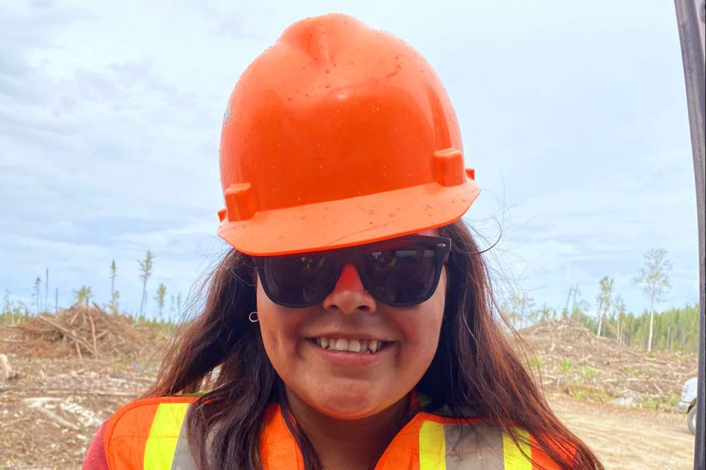 smiles, wearing a hard hat, sunglasses and vest