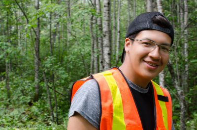 A young person smiling in the forest, wearing a vest
