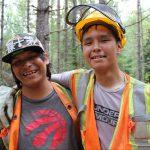 Dans la forêt, un jeune, portant un gilet de sécurité, des gants et un casque, met son bras autour de son ami, qui porte aussi un gilet de sécurité.