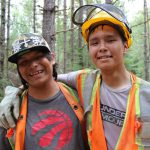 In the forest, a young person, wearing a safety vest, gloves, and helmet, puts his arm around his friend, who is also wearing a vest