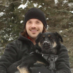 Mark Kmill holding a dog in the forest