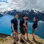 Quatre jeunes debout sur une falaise surplombant un lac et des montagnes