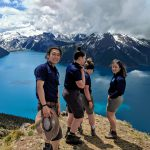 Four youth stand on a cliff overlooking a lake and moutains