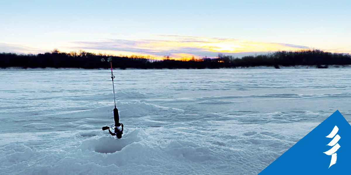 A fishing rod standing upright next to a hole in the ice.