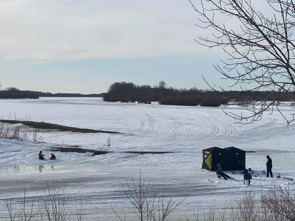 A family sitting around an ice fishing hole, next to an ice fishing tent
