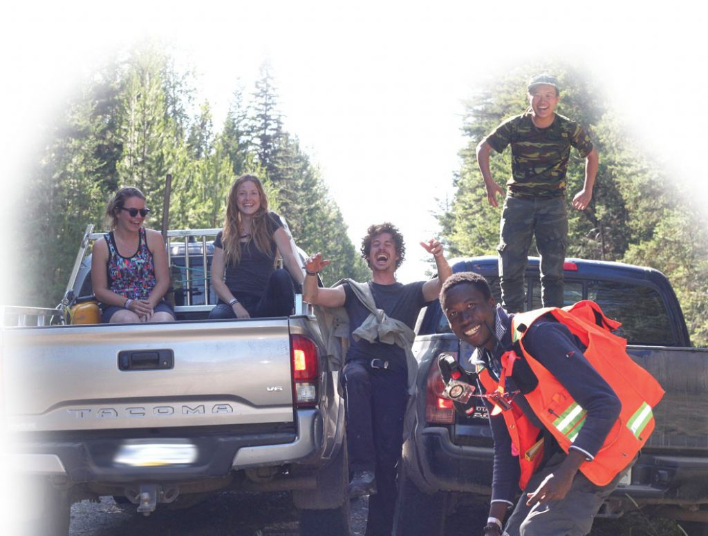 Youth hanging out in the forest with two pickup trucks