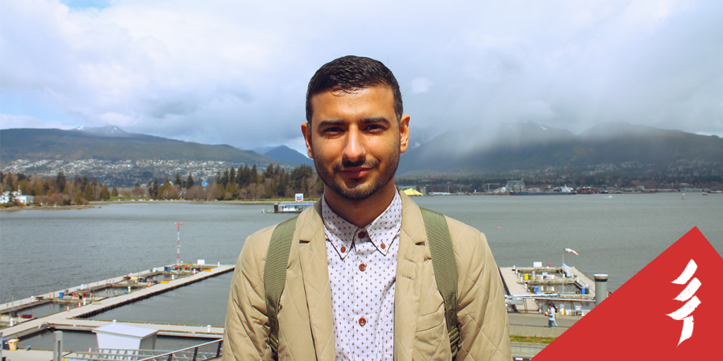 Ahmed looking at the camera, in front of docks and a body of water