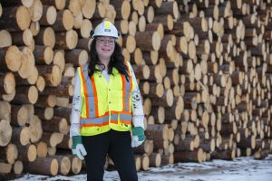 Amy Rose stands in front of logs, wearing a hard hat and vest