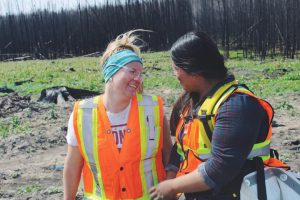 Two young women in safety vests looking at each other and laughing
