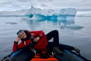 A young woman lying across a raft on a body of water, and iceberg behind her
