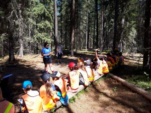 Young people sit on a log in a forest and listen to an educator