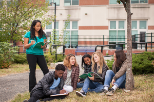Five high school students, sitting on the ground outside, read a textbook. Their instructor stands beside them.