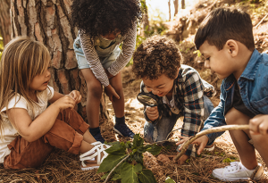 Four young children gathered around a lead, inspecting it with a magnifying glass