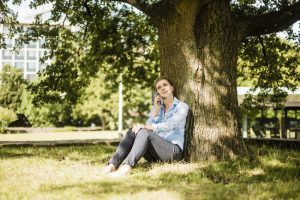 A young person on the phone, sitting at the base of a tree