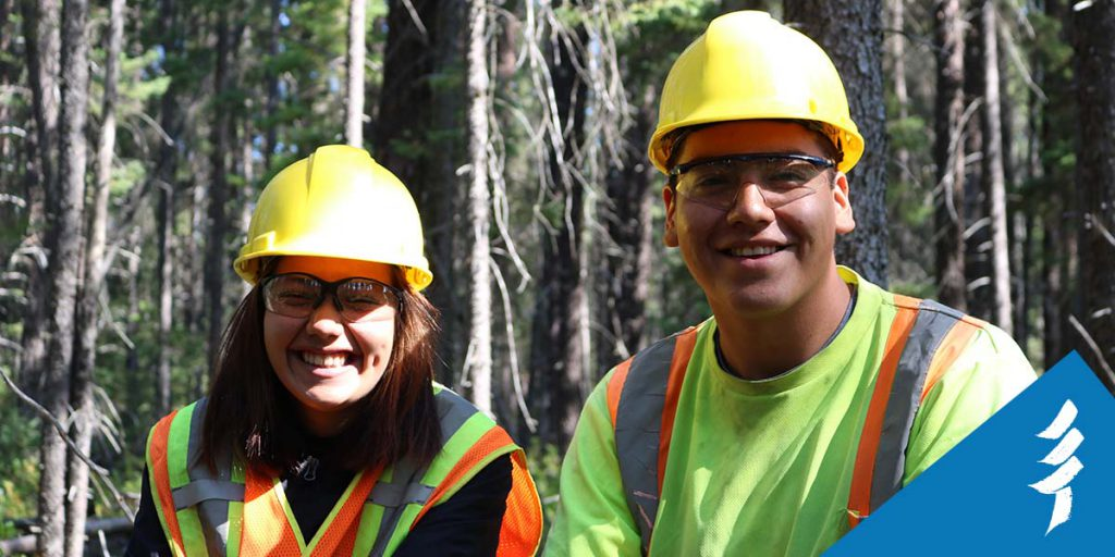 A young woman and man smiling at the camera, wearing hard hats, safety glasses, and vests